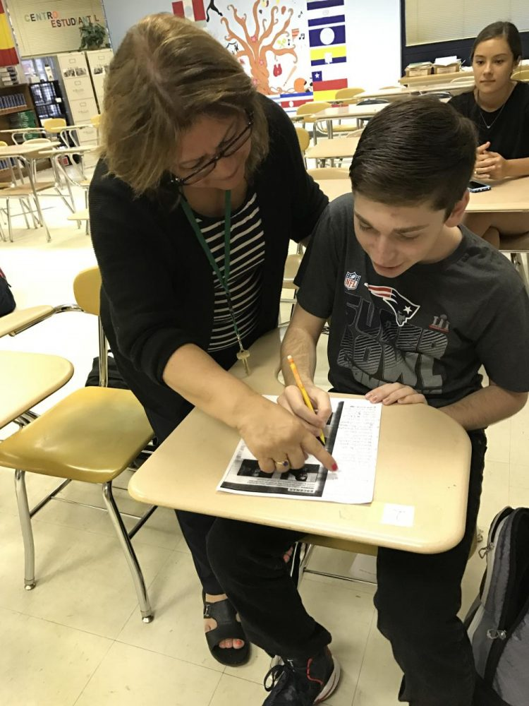 Helping+one+of+her+IB+Spanish+students%2C+Danny+Andrussier%2C+Mrs.+Hernandez+goes+in+depth+to+explain+the+work.+She+has+such+a+deep+love+for+teaching+language+and+culture+that+she+has+been+named+the+department+chair+for+World+Language%21+%0A