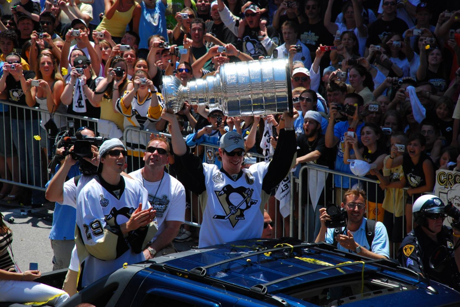 Celebrating during a parade during their last Stanley Cup win, Sidney Crosby holds the Stanley Cup above his head. The Penguins have won the cup in back-to-back years, and this is Crosby's third time hoisting it in celebration.