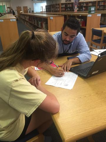 During lunch, teacher Mr. Bran tutors sophomore Izzy Morgan one-on-one in the library. Mr. Bran often dedicates his time to helping his students.