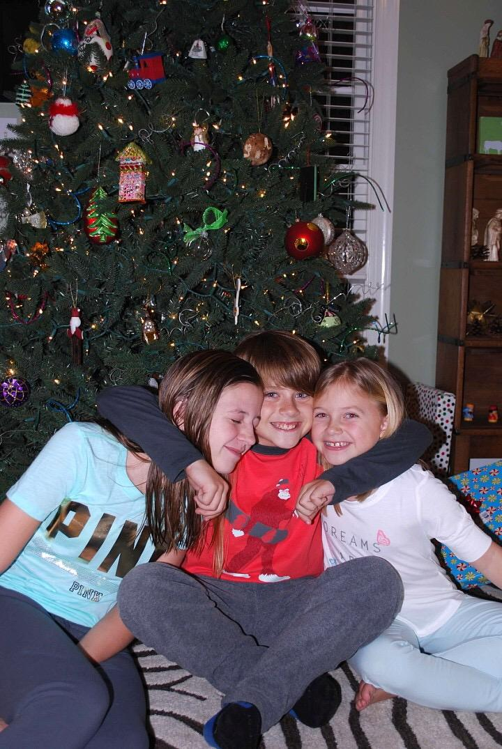 Enjoying each others company in front of the Christmas tree; Grayson McClendon, on the left, and her family have their own unique way of celebrating Christmas. With so many different customs and traditions, Christmas is a truly secular holiday.