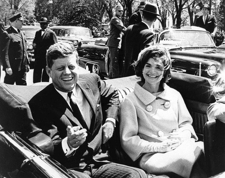 Riding in the motorcade just prior to his assassination, President John F. Kennedy smiles at the crowd in Dallas, Texas. Tomorrow President Trump is releasing the classified files about the assassination.