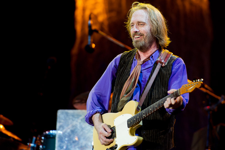 Playing his guitar, musician Tom Petty is able to wow his audience with hits like