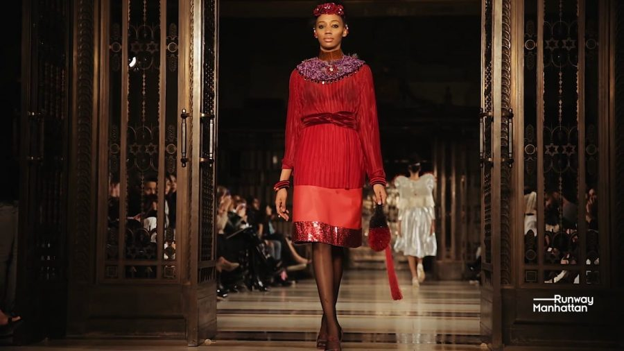 Strutting down the runway, the model stares ahead dressed in new trends at Fall Fashion Week 2017. The outfit combines red and fringe to encapsulate this year's autumn style trends.