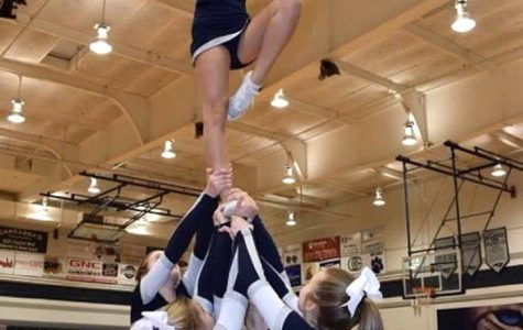 Hitting a lib in an extension, cheerleader Jesse Crossland uses strength and balance while being in the air on one foot. This is one of many stunts that cheerleaders do.