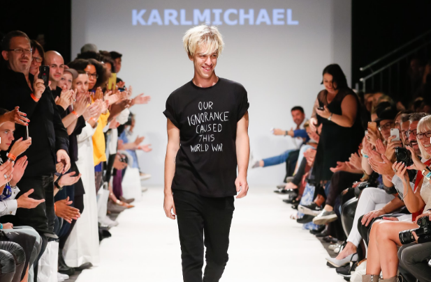 Strutting down the runway, an Austrian model for Karl Michael ignites a standing ovation with his daring statement t-shirt. Statement shirts were all the rage throughout 2017, since they let opinions be shared easily.