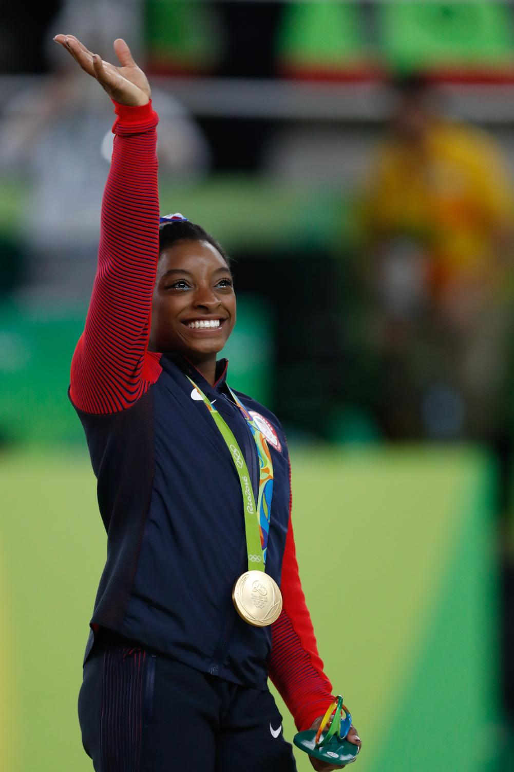 Waving at the crowd, Team USA gymnast Simone Biles celebrates a gold medal victory. Simone Biles was one of the female athletes to come out and accuse Dr. Nasser of sexual assault.