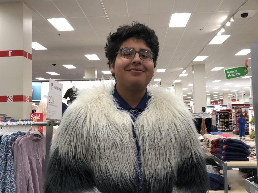 Smiling for the camera, junior Jonathan Alvarez dons a heavy feathery coat. Feathers have been all the rage for the winter season due to the luxurious look and feel they give off.