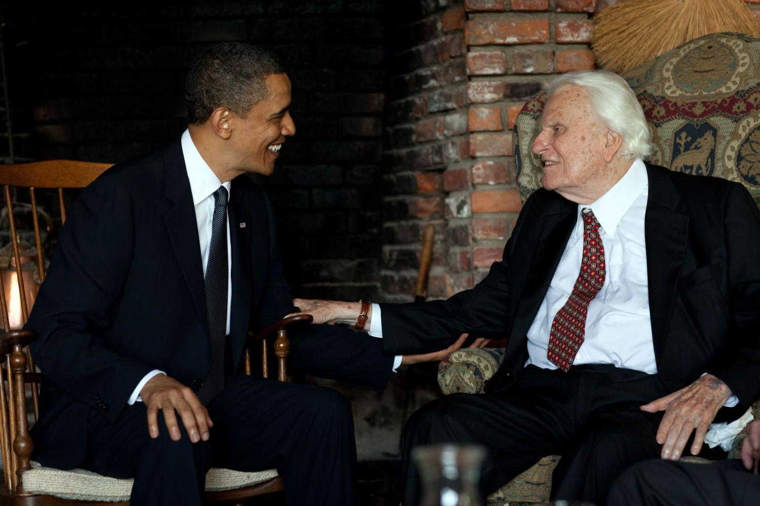 Meeting with former president Barack Obama, Billy Graham has a discussion in his home in Montreat, North Carolina. Graham recently passed away at age ninety-nine, leaving an evangelical legacy behind him.