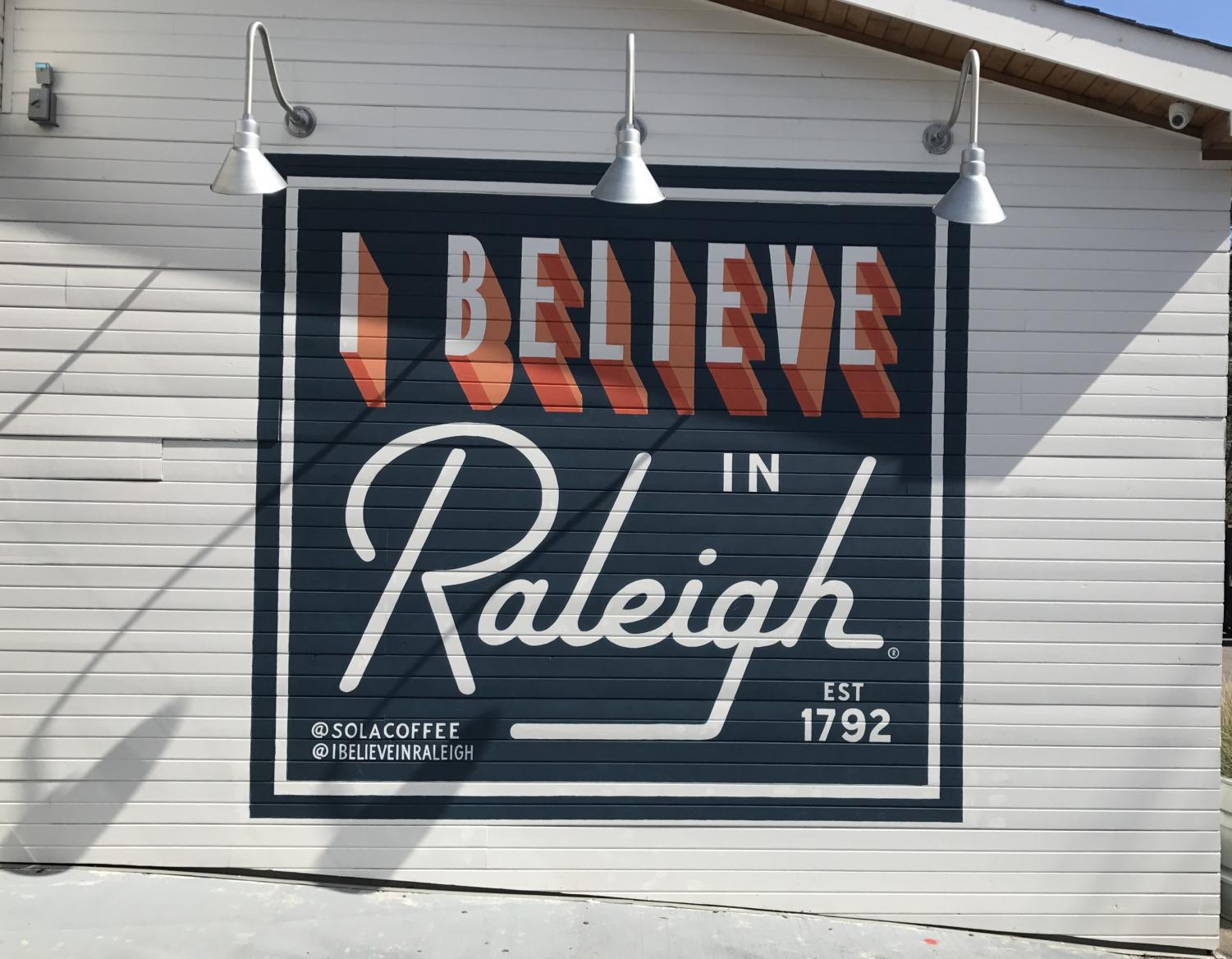 Representing the I Believe in Raleigh movement, the mural is painted across the back of the picturesque Sola Coffee Café. Sola is the perfect place for anyone looking for a cozy, laid-back dining experience and a taste of some of the best food in Raleigh.