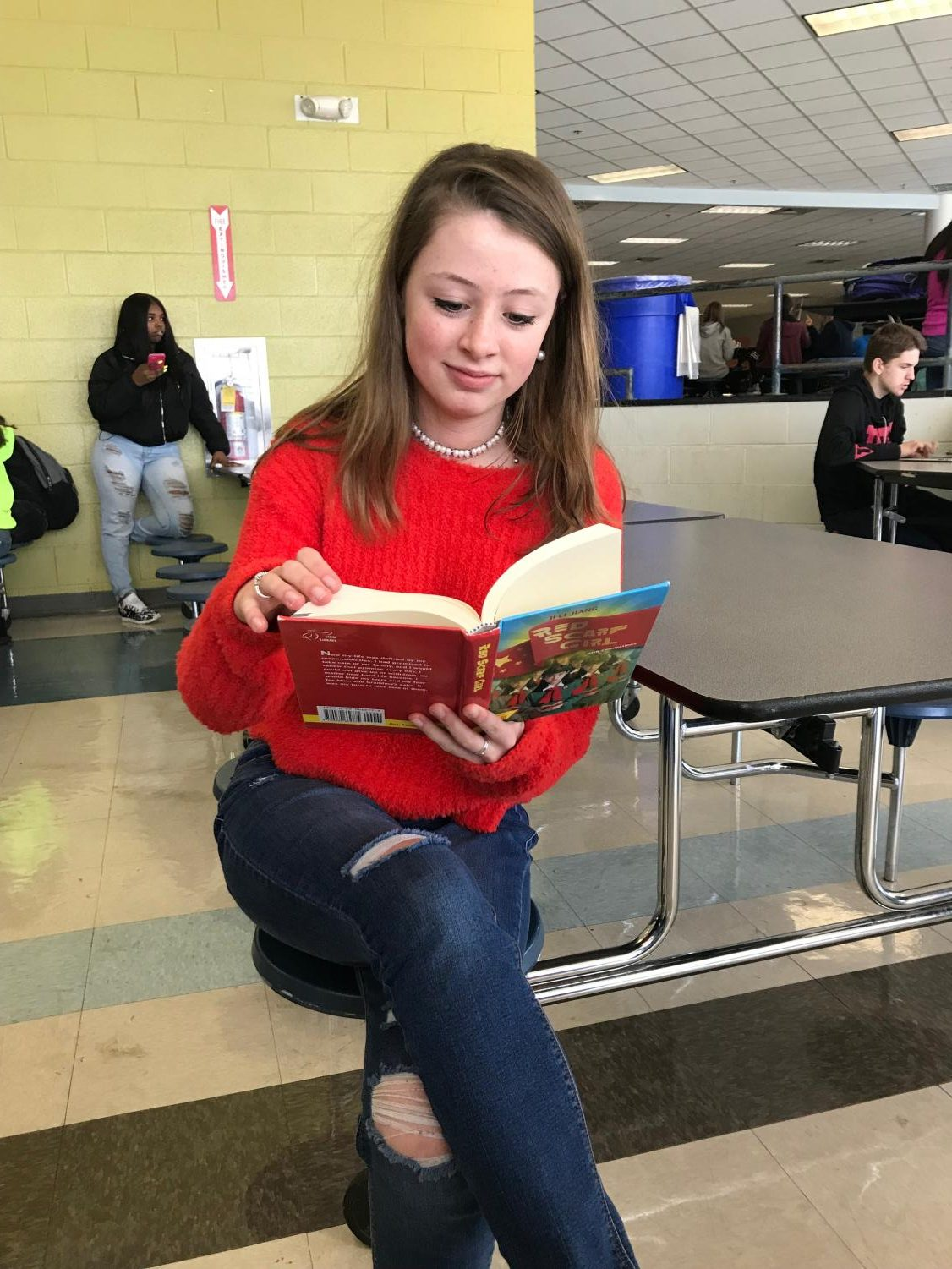 Reading a paperback book, Lily Morrow sits in the cafeteria oblivious to the world around her and absorbed with the story she is reading. This is just one example of how books and reading can impact our lives.