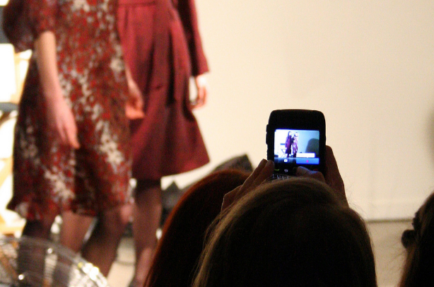 Strutting down the runway wearing trendy dresses, the models are captured on an audience member's cell phone. Thanks to social media, fashion can be documented quickly for others to view and draw inspiration from.