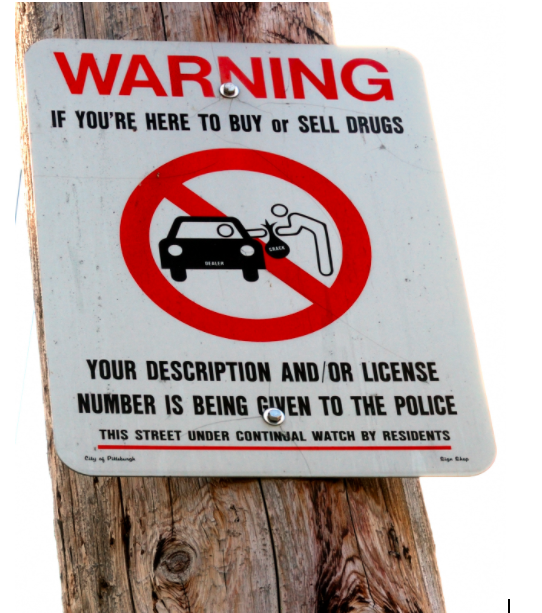 One+of+many+examples+of+the+criminalization+of+drug+use%2C+this+sign+prohibits+the+exchange+of+drugs.+However%2C+many+are+proposing+a+new+approach+in+which+there+are+safe+sites+for+addicts+to+take+their+drug+with+clean+needles+and+information+about+rehabilitation.