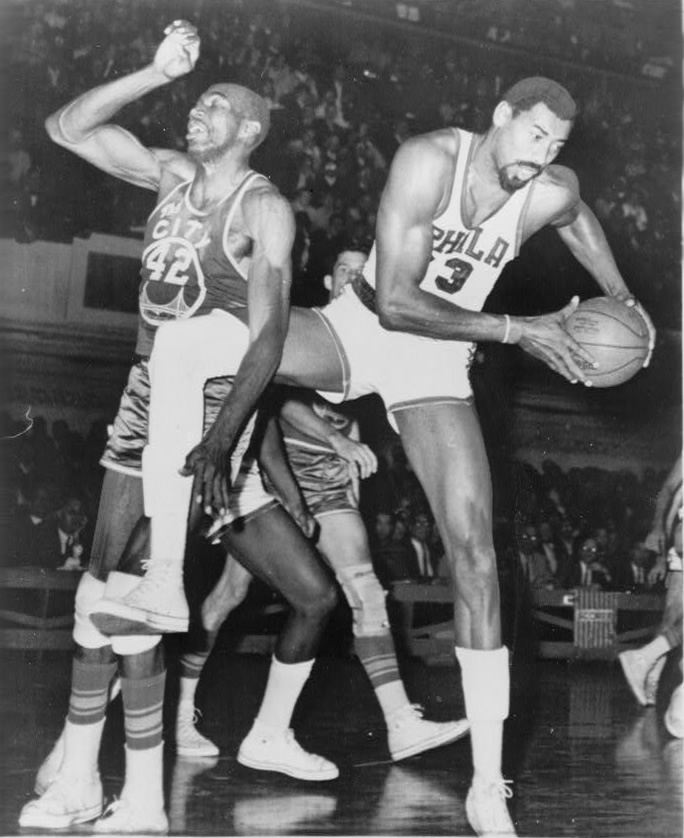 Coming down with a rebound, Wilt Chamberlain plays in a game for the Philadelphia 76ers. Chamberlain is the leader in rebounds per game over a career and rebounds in a single game.