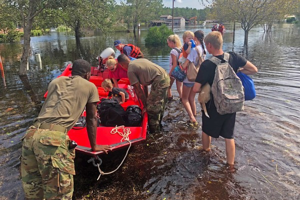 Fleeing their home, a family of Wilmington residents leave their house to escape the flooding with help from the North Carolina National Guard. Over a week after the deadly Hurricane Florence, people still remain in shelters because of the damage.
