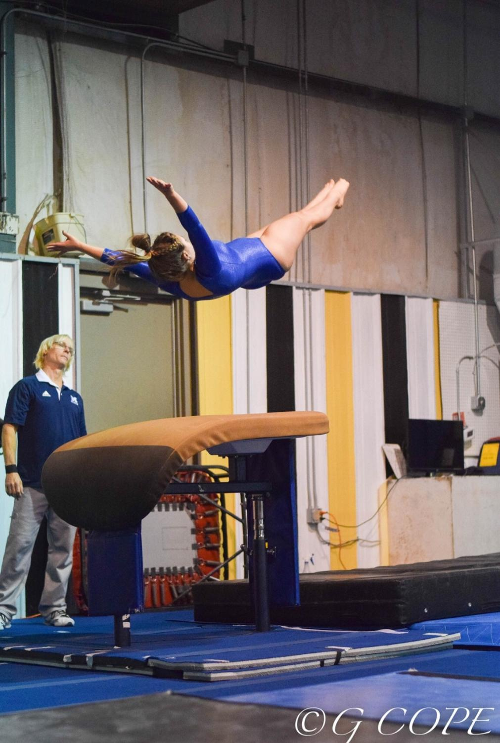 Thrusting herself into the air, senior Andrea Shealey executes a challenging vault routine. As captain, she commends her teammates for their enthusiasm and support of one another.