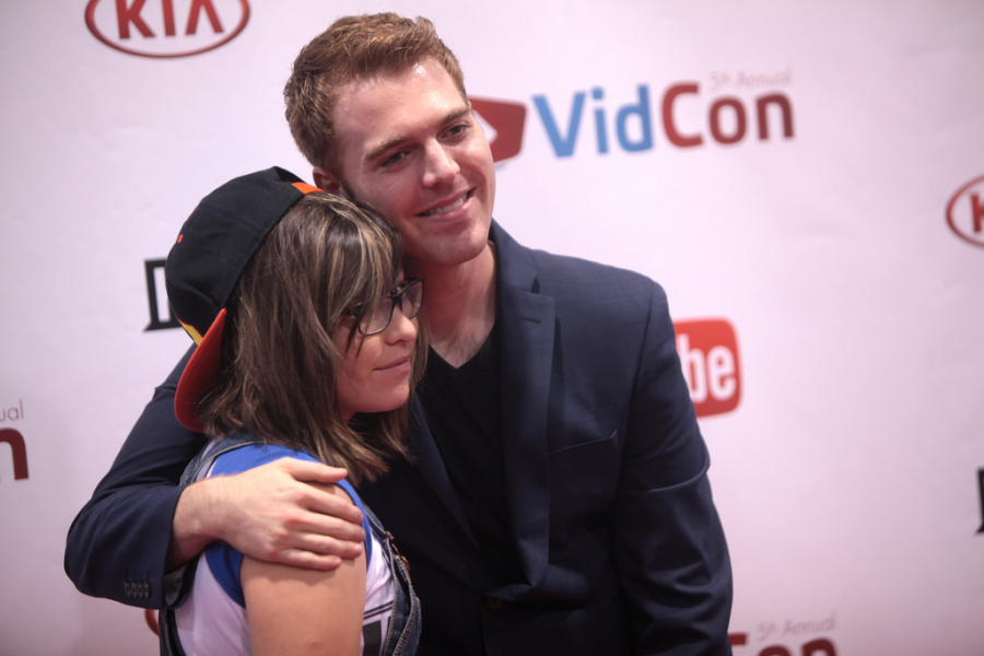 Smiling, Shane takes a photo with a fan at Vidcon in 2014. This is all before Shane became more popular and began filming his videos about other YouTubers.