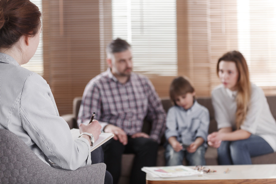 Talking about the child's mental health, two parents sit down with their son's school psychologist to discuss ways to help him. A child needs to have the right resources in order to help them develop properly.