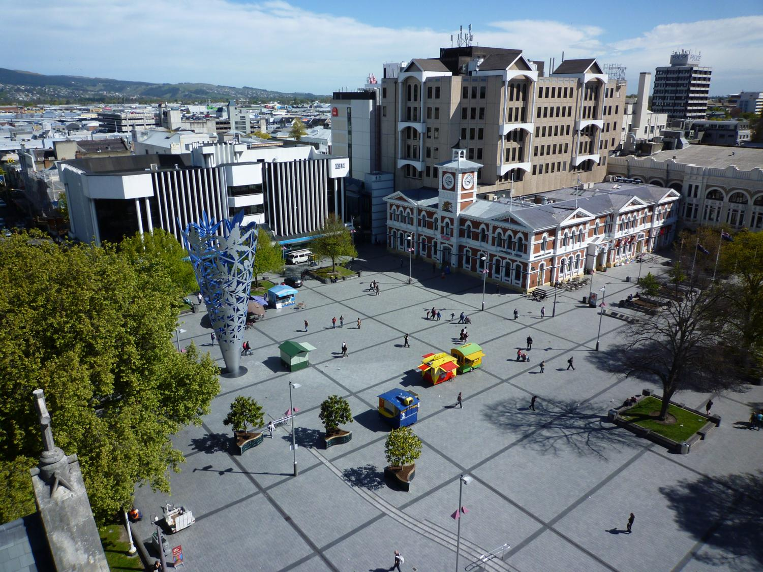 Touring the plaza, locals and tourists explore Cathedral Square in Christchurch, New Zealand. On Friday morning, this square was in total chaos because of two shootings that left dozens dead.