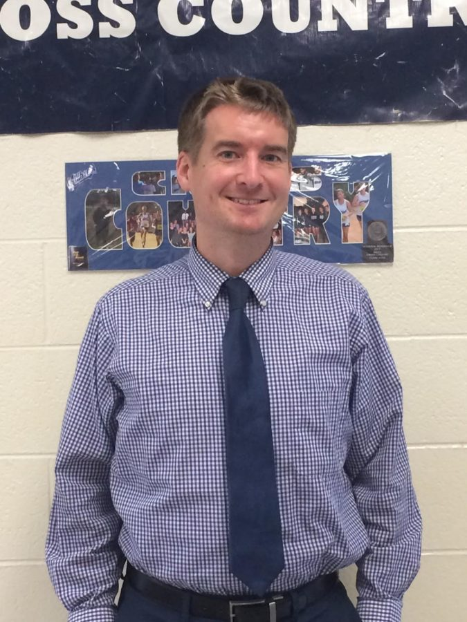 Standing proudly in front of his cross country poster, Mr. Adams is a great example of what it means to teach. Mr. Adams has an undying passion for teaching and helping his students prepare for their first steps in the real world.