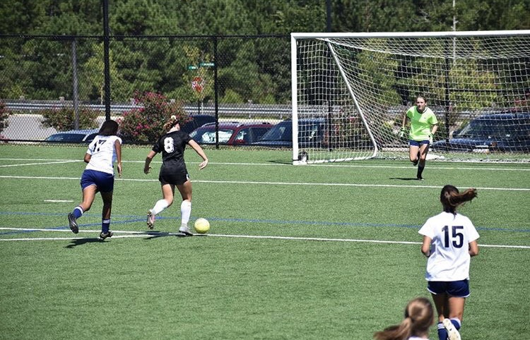 Running up to stop the offender, Rebecca High attempts to block the ball as goalie. Rebecca plays soccer outside of school and will be a part of the Junior Varsity team this upcoming season.