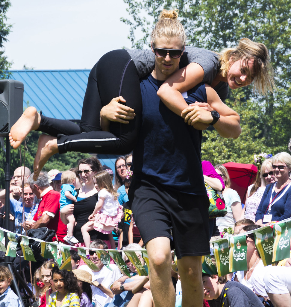 Running fast around the course, this man carries his partner in a Wife Carrying competition. Wife Carrying is an uncommon sport typically played in England, France, and the United States.
