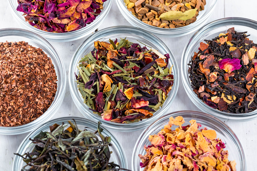 Placed in small bowls, loose leaf tea is arranged in a circular fashion. Tea is made with dried leaves and hot water, displaying its advantageous aspect of being a natural method to improve health.
