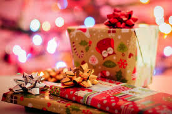 Illuminated by Christmas tree lights, presents sit neatly underneath the tree. Getting a Christmas tree specifically for a gift exchange can add to this tradition and take it to the next level.