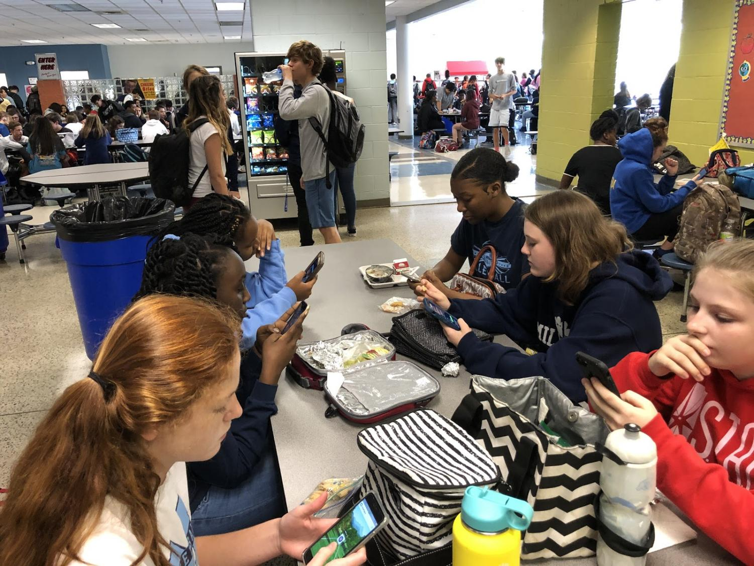 Playing on their phones, Millbrook freshman Hannah Rose Morrow, Mary Katherine Boone, among many others catch up on social media during their lunchtime. As much fun as phones are, they can also be blocking teens from doing schoolwork, chores, and interacting with others, therefore lowering their overall work ethic and motivation for everyday tasks.
