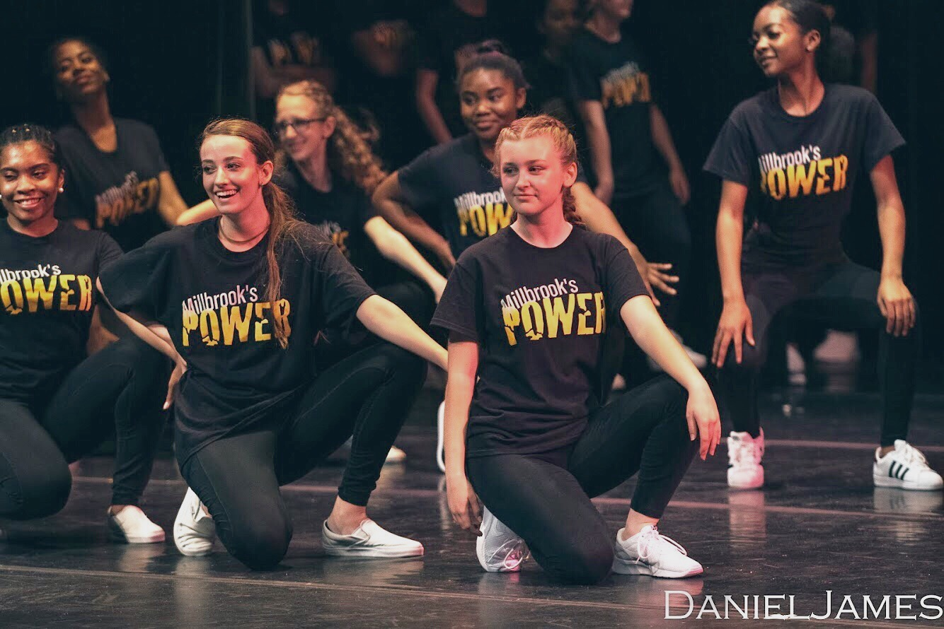 """Posing in her """"Power"""" shirt, senior Mackenzie Hudson gives the audience a grin at the end of the dance concert last spring. The dance department is one of many aspects that makes Millbrook so amazing."""