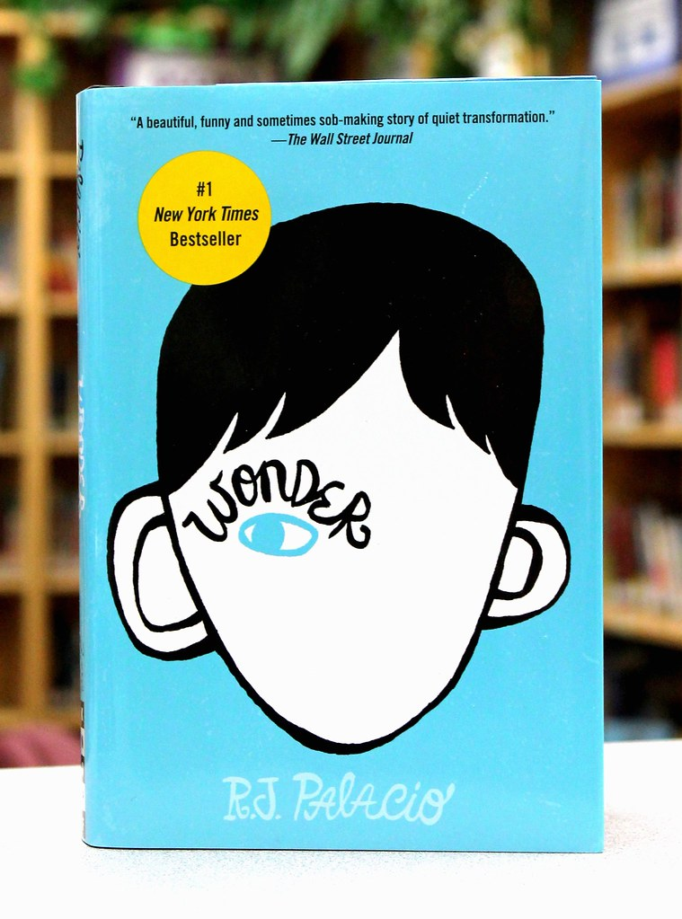 Standing against the backdrop of a school library, Wonder boasts a #1 New York Times Bestseller sticker. This novel can be found in nearly any library or bookstore near you.