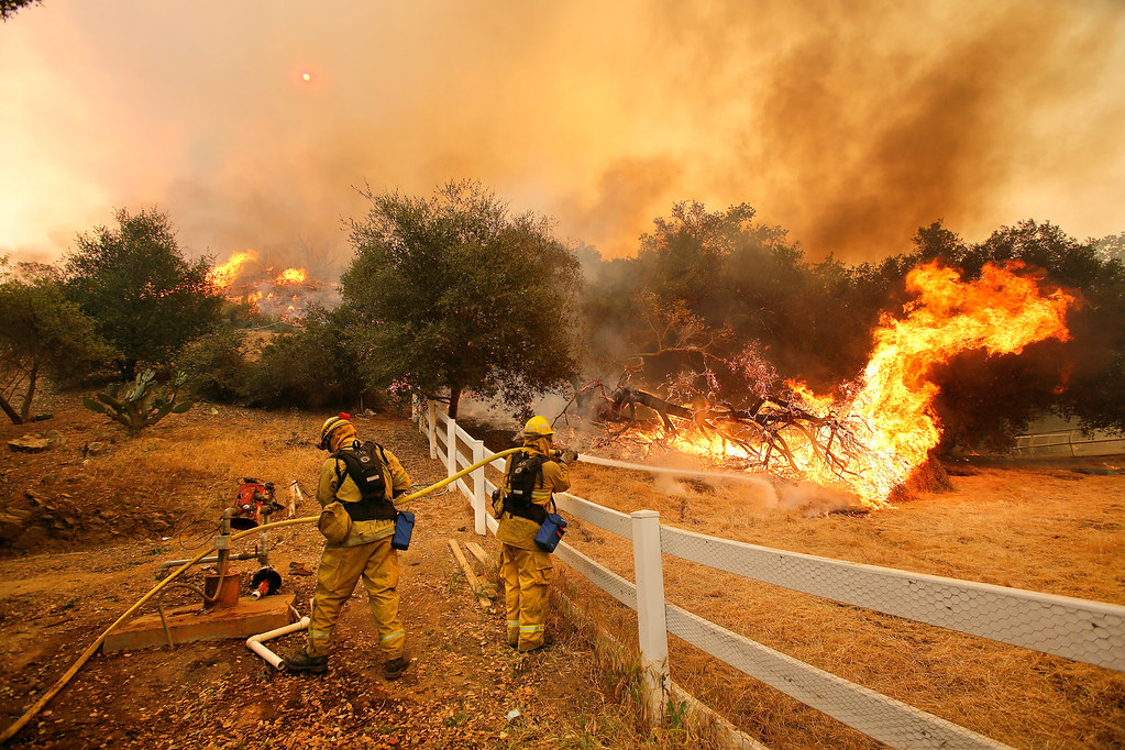 Dowsing water into the air, these firefighters in Stockton, California attempt to prevent a wildfire from diverting towards people and property. Extreme weather such as fires and hurricanes have become more frequent in recent years partly due to changes in the environment.
