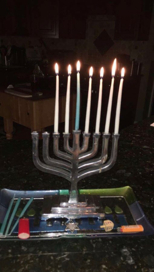 Flickering through the holiday, senior Landon Smith's menorah shows only six candles lit with the two left for the last two days. The menorah typically has nine candle holders, eight of which represent the Hanukkah miracle and the one in the middle acting as a lighter for the others.