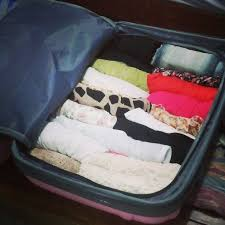 Organized in an orderly fashion, the suitcase contains rolled clothes to allow for more space. The traveler will be able to pack everything they want by freeing up this section of their bag.