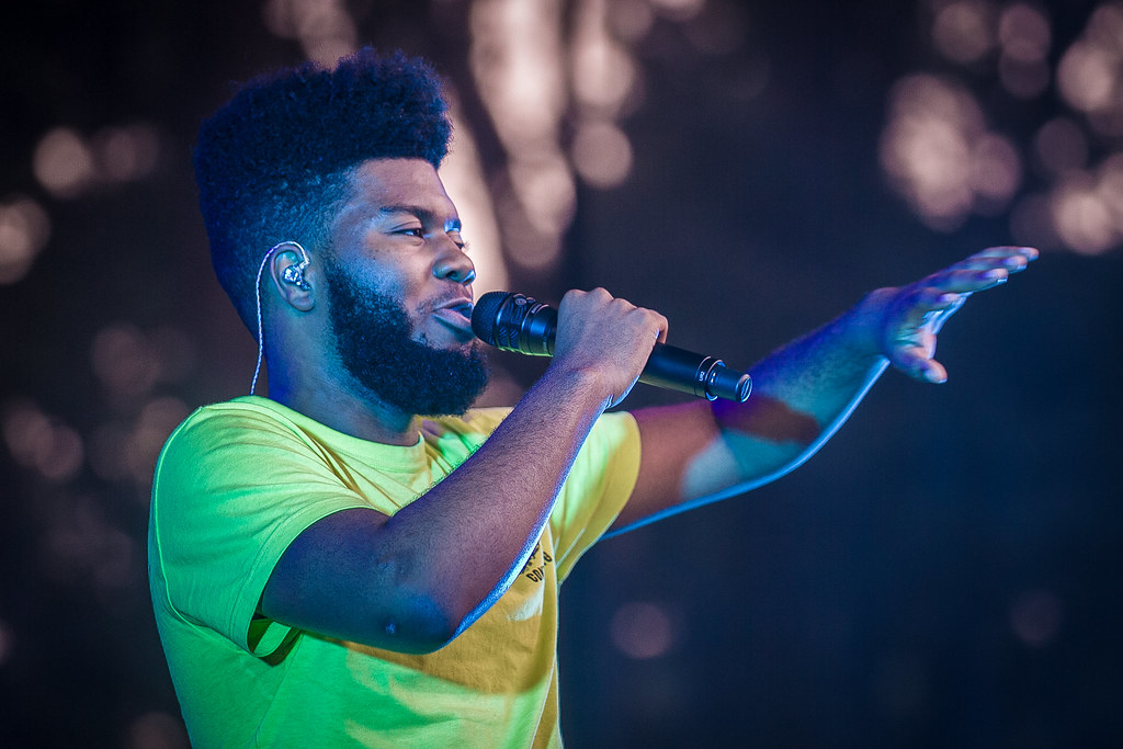 Performing at a concert, Khalid sings in front of the crowd. Khalid has created countless hit songs and was named one of the most influential people of 2019; his authenticity is something that he is respected for.