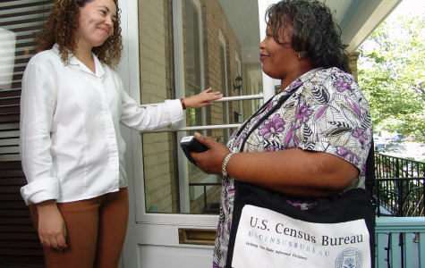 Taking responses from a woman on her front porch, this Census worker is tasked with getting accurate data about population size and demographics within each household. The survey is used to allocate electoral votes and funding for goods in public use, such as healthcare, education and public transportation.