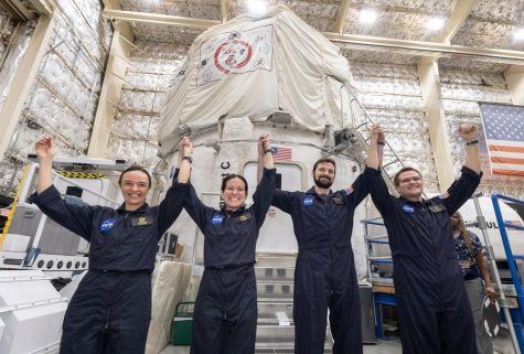 Holding their hands in the air, the four members of the Mars Mission smile proudly. The chosen ones stand ready to take the picture in commemoration of their first group meeting since they volunteered.