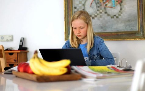 Focusing on the screen, a student engages with school activities from the comfort of her home. Learning virtually from home can be challenging when it feels like you are constantly connected, so taking breaks is important for eye and overall health.