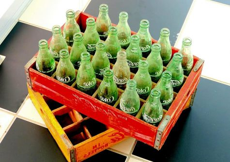 Nestled in wooden crates are vintage glass Coke bottles. Glass soda bottles like these, made from renewable material, are one way that we can learn from the past about being more eco-friendly and to assess changes we can make today.