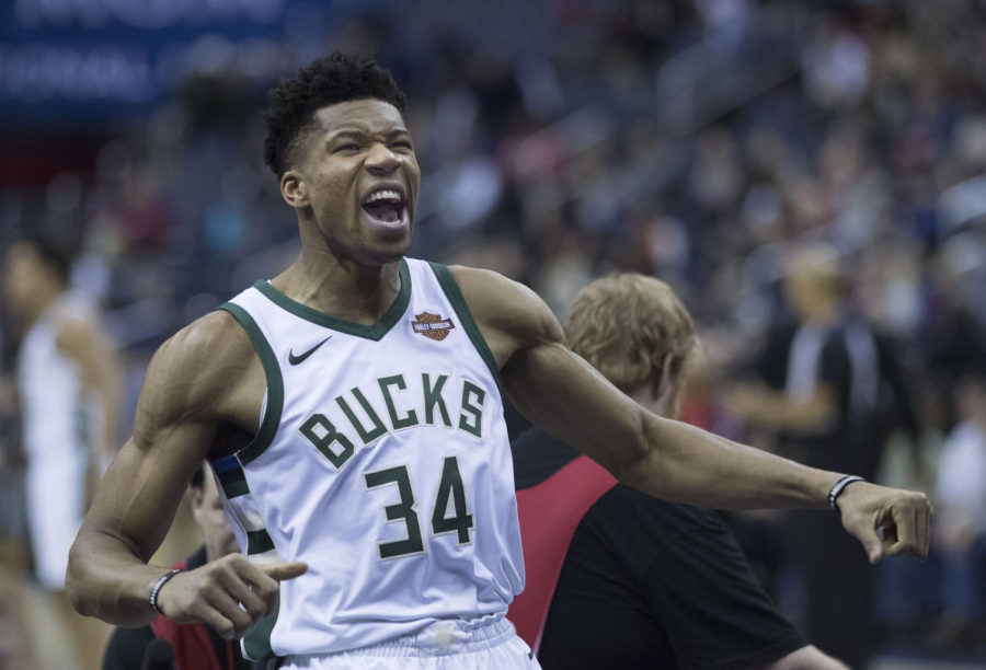 Celebrating after a big play on the offensive end, Giannis Antetokounmpo flexes his muscles at the opposing crowd. Antetokounmpo was given his second-straight MVP trophy after a record-setting season in which he averaged the lowest minutes per game in the award's history.
