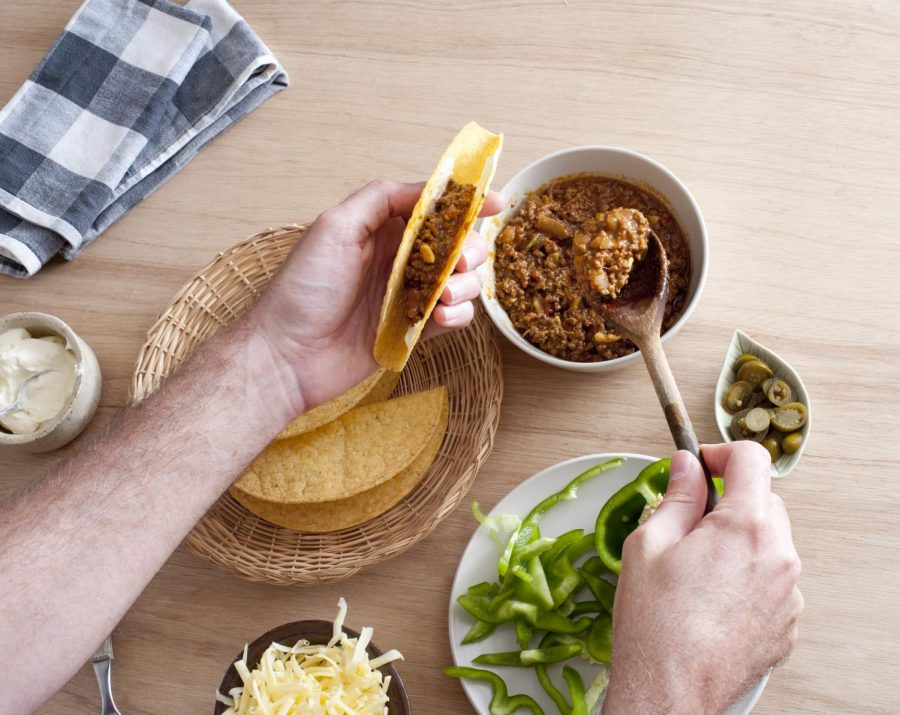 Preparing a meal, this person generously fills their taco with desired toppings. Many restaurants, like Bartaco, are providing a take-home meal kit option so their food can still be enjoyed in the comfort of customers' homes during the pandemic.