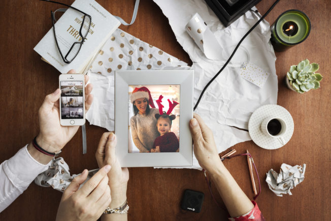 Unwrapping a gift, the recipient holds a sentimental framed photo. While most photos are digital, printing photos or making a scrapbook for family and friends can make a thoughtful and useful gift.