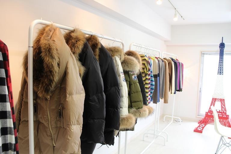 Various winter clothing items hang on racks, ready for shoppers to purchase for the season. These fur-lined puffer coats, gingham shirts, and other neutral tone items represent a few of the many fabulous fashion trends in the winter 2020/2021 season.