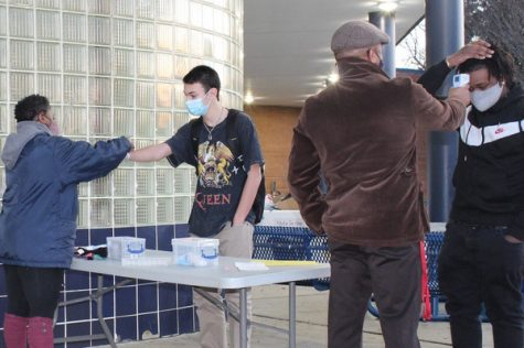 Standing six-feet apart, checking temperatures, and putting on wristbands, Mr. Dowden and Ms. Clarke helps students re-enter the building after one year of online learning. Students learn the new rules and regulations as starting a new and very unfamiliar journey, and begin adjusting to the new normal.