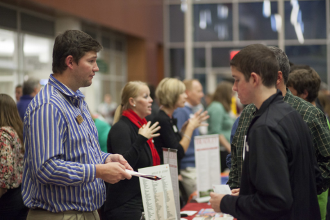 Meeting with representatives from a prospective college, students gather information about grade requirements and majors offered at a college fair. Millbrook hosts its own annual college visits for public universities in NC to meet interested students.