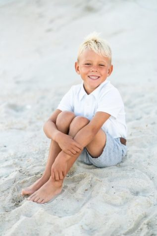 Sitting on the sand of Topsail Beach, six-year-old Aven Moffat smiles widely at his family. Topsail was a place that the Moffat family has always used to get away, and it became one of Aven's favorite places.